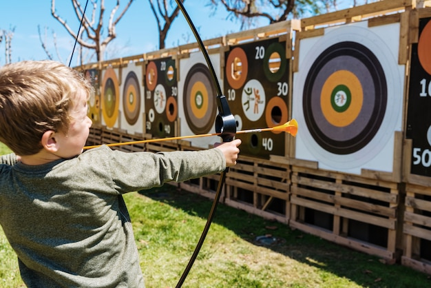 Kind, das mit einem bogen und pfeilen spielt, die sie gegen ein bullauge werfen.