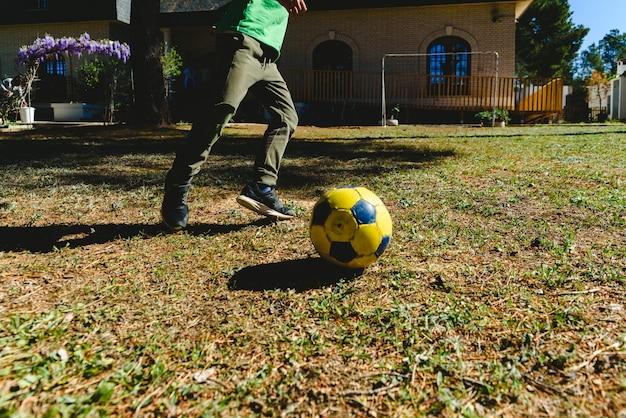 Kind, das mit einem fußball im yard seines hauses in der sonne spielt.