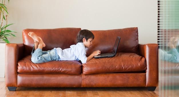 Kind, das mit einem laptop auf dem sofa spielt