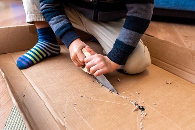 Kind, das mit einer pappschachtel und einer säge spielt, um zu errichten