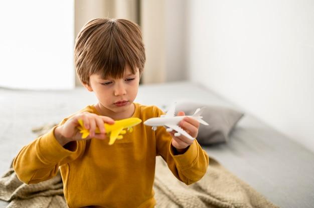 Kind, das mit flugzeugfiguren spielt