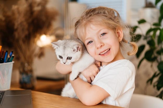Kind, das mit kleiner katze spielt ein kleines mädchen hält ein weißes kätzchen. ein kleines mädchen kuschelt sich an ein süßes haustier und lächelt, während es im wohnzimmer des hauses sitzt. glückliche kinder und haustiere.