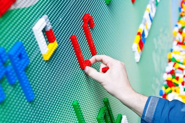 Kind, das mit plastikspielzeugziegelsteinen spielt
