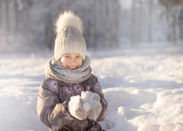 Kind, das mit schnee im winter spielt. kinder fangen schneeflocken