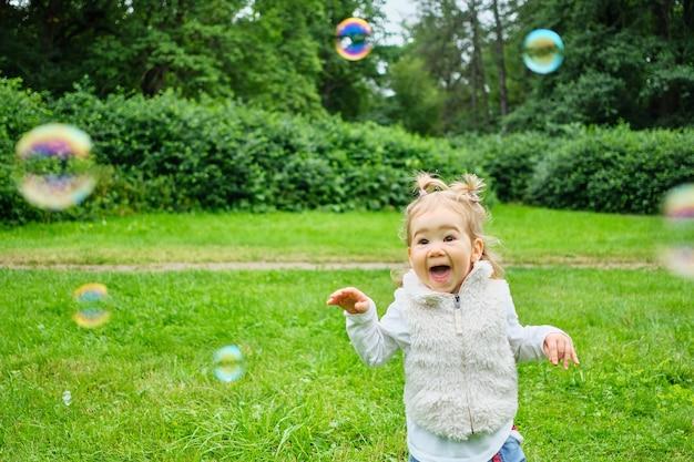 Kind, das mit seifenblasen im park spielt