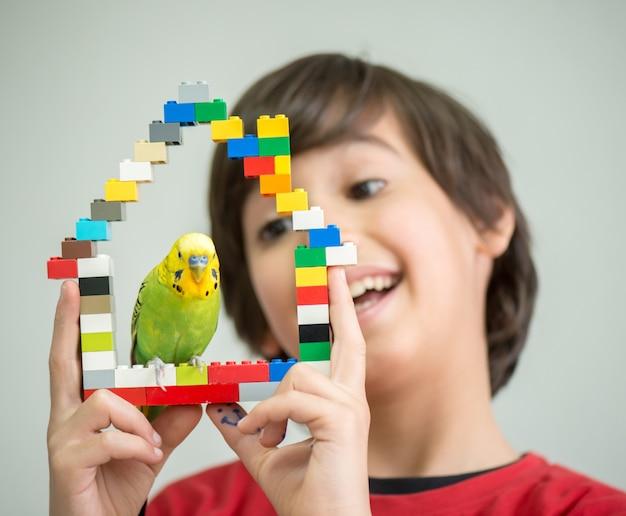 Kind, das mit seinem haustierpapageien spielt