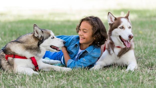 Kind, das mit seinen hunden spielt, während draußen mit familie