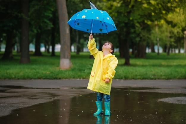 Kind, das mit spielzeugboot in der pfütze spielt. kinder spielen im freien bei regen. herbst regnerisches wetter im freien aktivität für kleine kinder.