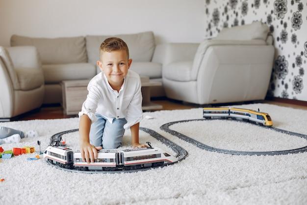 Kind, das mit spielzeugzug in einem spielzimmer spielt