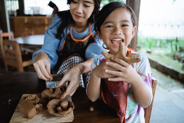 Kind, das mit ton arbeitet, das keramik macht