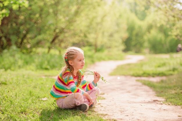 Kind, das nahe straße mit blume sitzt