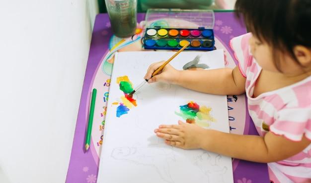 Kind, das pinsel für das malen mit kunstwerk verwendet, das für das verbessern der handschrift s gut ist