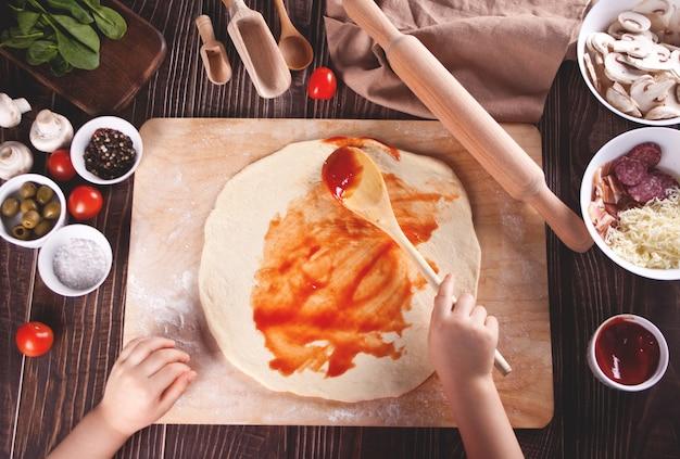 Kind, das pizza in der hauptküche macht