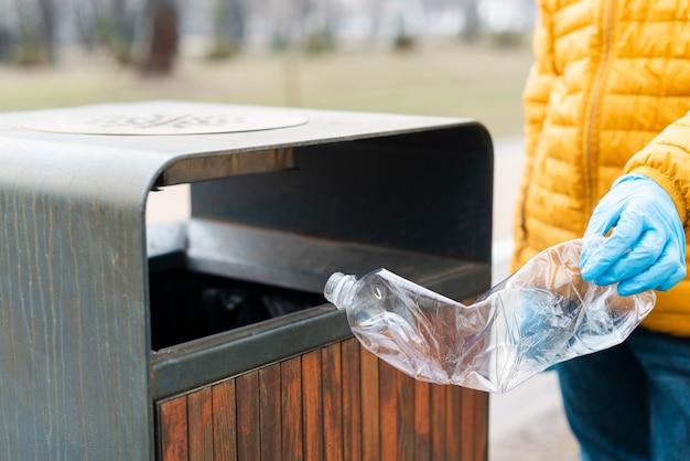 Kind, das plastikflasche in papierkorb wirft