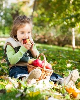 Kind, das roten apfel im herbstpark isst