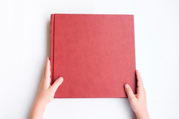 Kind, das rotes leder bedecktes fotobuch hält