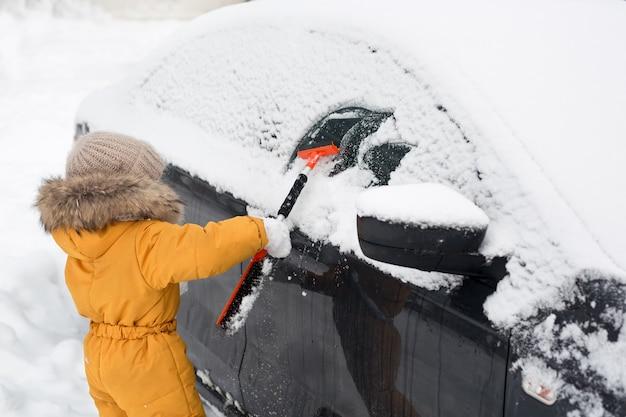 Kind, das schnee vom auto nach sturm bürstet