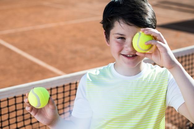 Kind, das sein auge mit tennisball bedeckt
