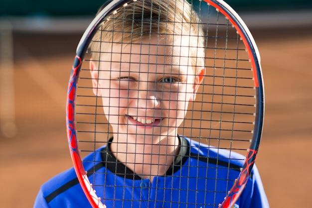 Kind, das sein gesicht mit einem tennisschläger bedeckt