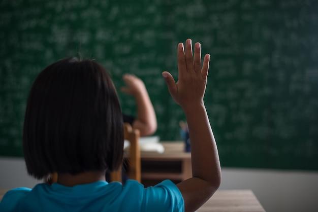 Kind, das seine hand im klassenzimmer anhebt