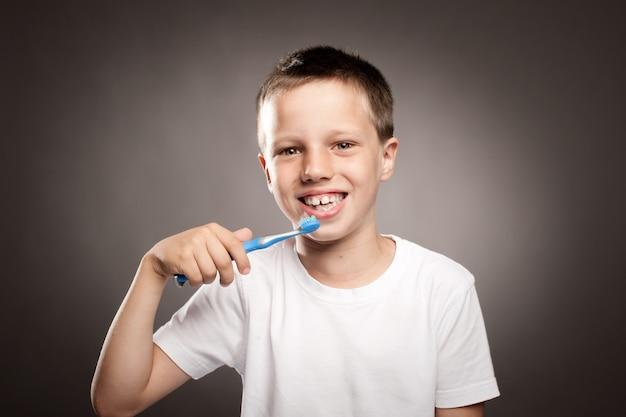 Kind, das seine zähne auf grau putzt