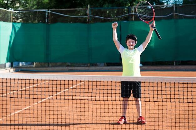 Kind, das sieg eines tennisspiels feiert