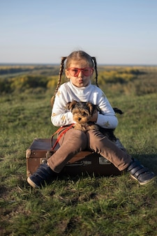 Kind, das sonnenbrille spielt, die mit ihrem hund spielt