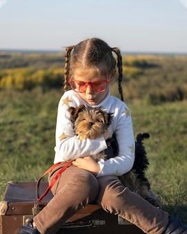 Kind, das sonnenbrille spielt, die mit ihrem hund vorderansicht spielt