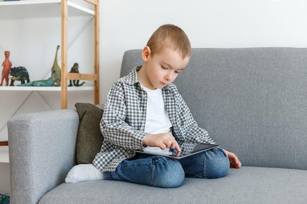 Kind, das spaß mit tablette hat, die auf einer couch sitzt