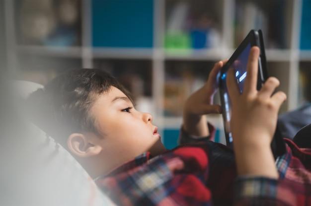 Kind, das spiel allein auf tablette spielt