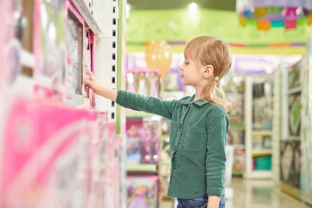Kind, das spielzeug für den kauf in einem großen geschäft auswählt.