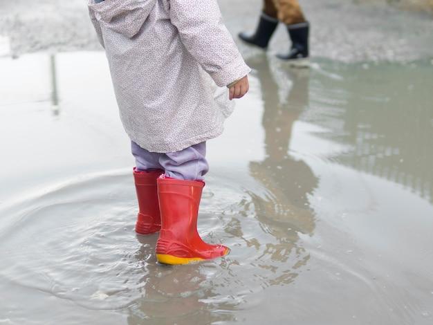Kind, das stiefel trägt und im wasser sitzt