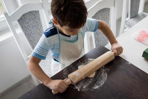 Kind, das teig für köstlichen bonbon bildet