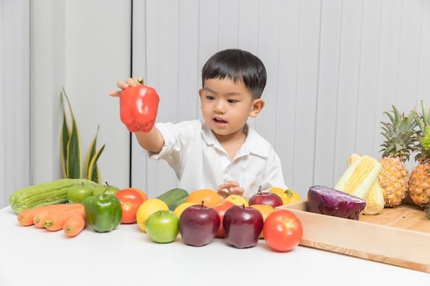 Kind, das über nahrung lernt, wie man frische obst und gemüse isst.