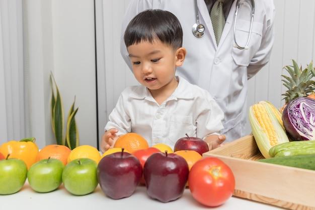 Kind, das über nahrung mit doktor lernt, um zu wählen, frische obst und gemüse essend.