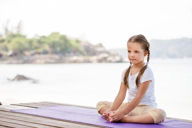 Kind, das übung auf plattform im freien macht. gesunder ozeanlebensstil. yoga mädchen