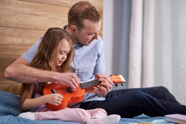 Kind, das ukulele spielt, während mit vater auf bett zu hause sitzt. porträt des jungen kaukasischen mannes, der kleine tochter lehrt, die gitarre spielt