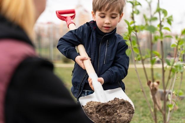 Kind, das versucht, einen baum im freien zu pflanzen