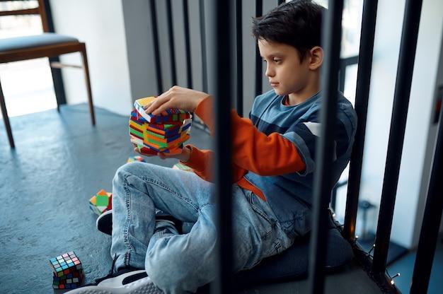 Kind, das versucht, schwierige puzzlespielwürfel zu lösen. spielzeug für gehirn- und logisches denktraining, kreatives spiel, lösung komplexer probleme
