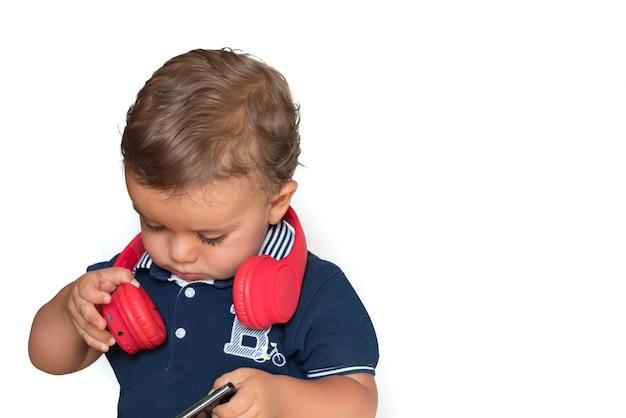 Kind, das videos auf handy mit roten kopfhörern und dunkelblauem hemd ansieht