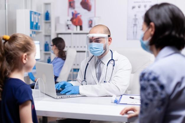 Kind, das während der ärztlichen untersuchung einen arzt mit gesichtsmaske gegen coronavirus ansieht. facharzt für medizin bietet beratung im gesundheitswesen, röntgenbehandlung in der klinik.