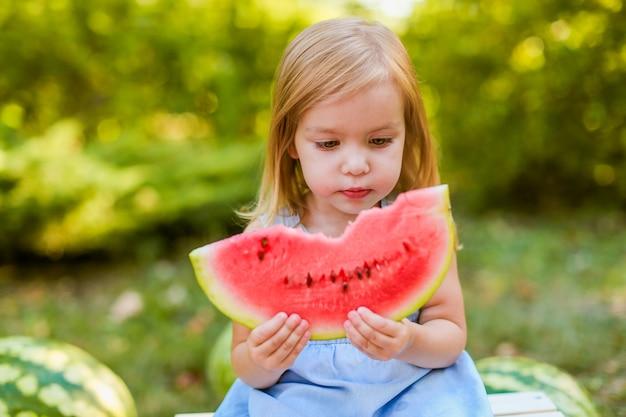 Kind, das wassermelone im garten isst. kinder essen obst im freien. gesunder snack für kinder. 2 jahre altes mädchen, das wassermelone genießt.