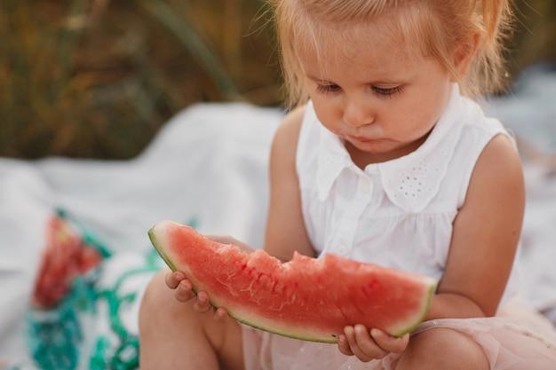 Kind, das wassermelone im garten isst. kinder essen obst im freien. gesunder snack für kinder. kleines mädchen, das im garten hält eine scheibe der wassermelone spielt. kid gartenarbeit