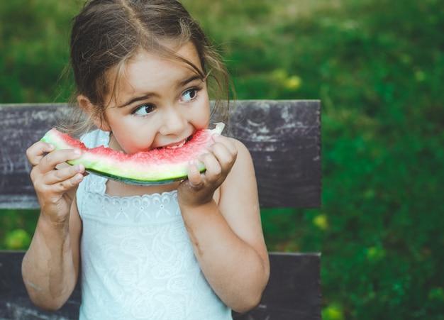 Kind, das wassermelone im garten isst. kinder essen obst im freien. gesunder snack für kinder. kleines mädchen, das im garten spielt und eine scheibe wassermelone beißt.