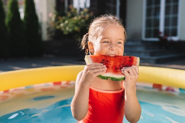 Kind, das wassermelone im pool im hof isst. kinder essen obst im freien. gesunder snack für kinder.