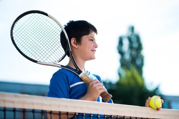 Kind, das weg auf dem tennisfeld schaut