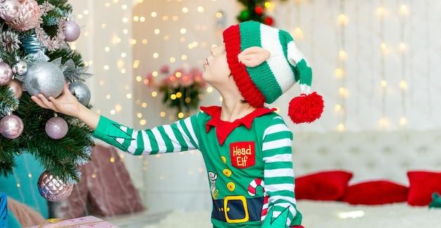 Kind, das weihnachtsbaum zu hause verziert