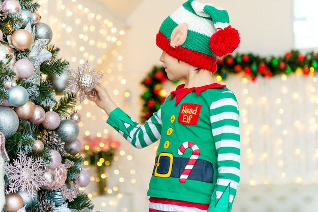 Kind, das weihnachtsbaum zu hause verziert Premium Fotos