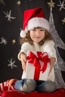 Kind, das weihnachtsgeschenk hält. weihnachtsferienkonzept Premium Fotos