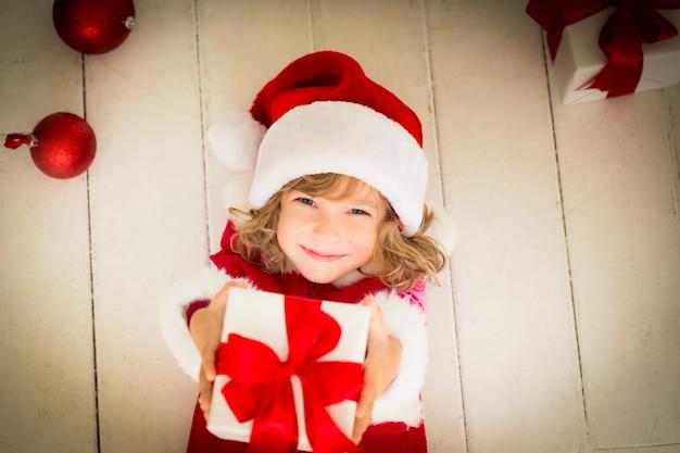 Kind, das weihnachtsgeschenk hält. weihnachtsferienkonzept